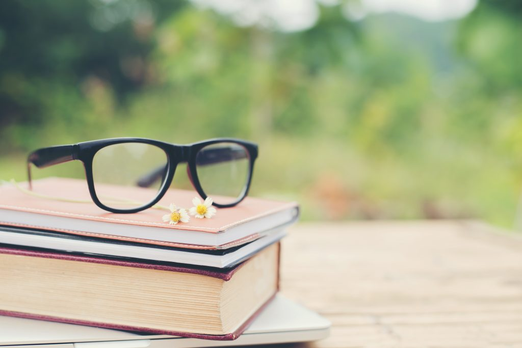 Book and eye glasses for read and write over blurred nature outd